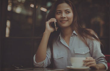 female sitting in a coffee shop with a cup of coffee talking on mobile phone